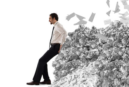 Businessman pushing with fatigue a big pile of paperwork Фото со стока