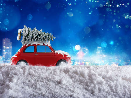 Christmas tree on the roof of a car driving on snow