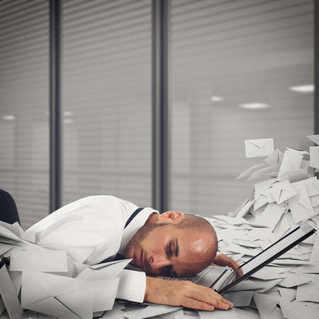 pain: Businessman on laptop with a pile of worksheets and mail. Buried by work concept