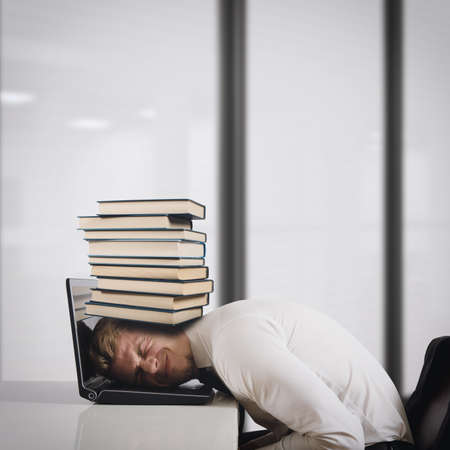 burdensome: Businessman on laptop with a pile of books on head. Oppressed by work concept Stock Photo