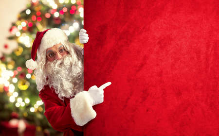 Santa Claus shows a big red billboard on xmas tree background