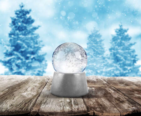 traditional: Xmas snowball on wooden planks on background with snowy landscape