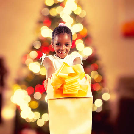 Happy little girl receives a big golden xmas gift and on background lights of the Christmas tree Stock Photo
