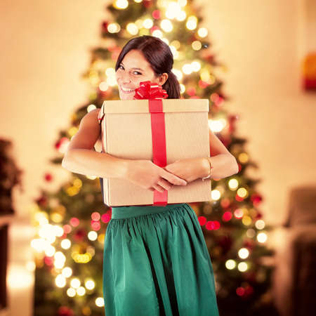 christmas gift: Happy woman receives a big xmas gift and on background lights of the Christmas tree