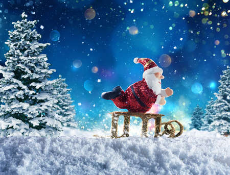 Cute puppet of Santa Claus plays with sleigh on the snow Stock Photo
