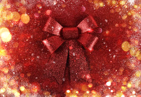Glittering red ribbon with bow for xmas on sparkly background Stock Photo