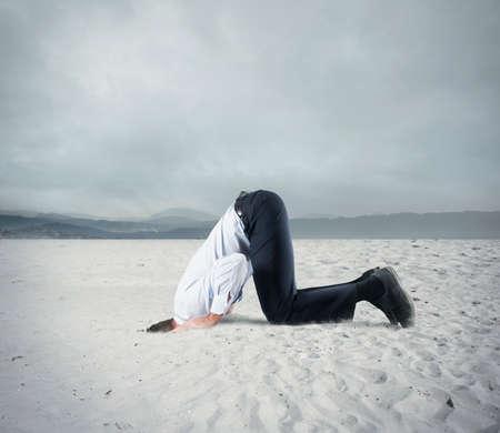恐れているビジネスマンは、ダチョウのように地面の下で彼の頭を隠します。危機概念の恐怖