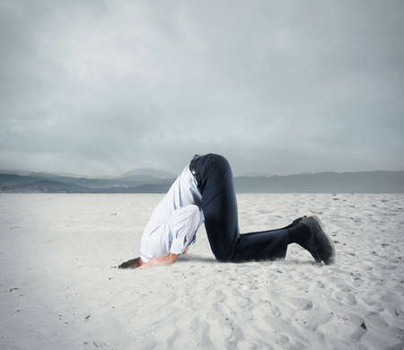 Afraid businessman hide his head under the ground like an ostrich. Fear of crisis concept Фото со стока