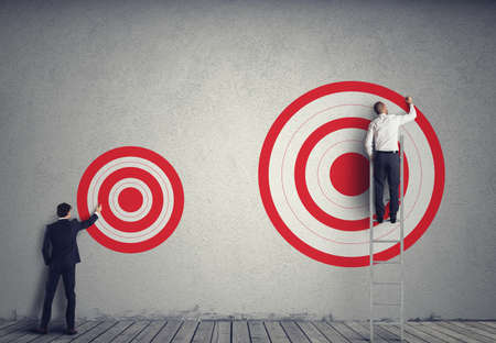 achieve: Businessman drawing a bigger target of his colleague. Achieve more important goals in work concept