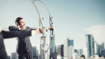 Businessmen in a competition with the arc and arrows to reach and hit new targets in a roof of skyscraper