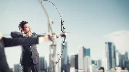 metas: Los hombres de negocios en una competición con el arco y las flechas para alcanzar y golpear nuevos objetivos en una azotea del rascacielos