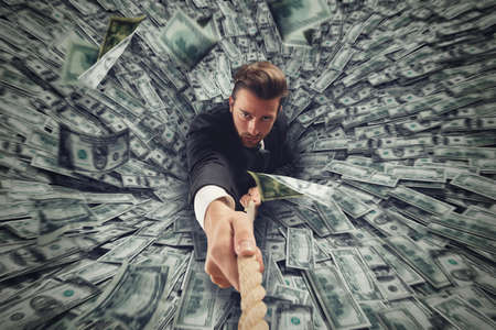 suck: Businessman swallowed by black hole of money Stock Photo