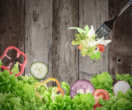 Background of mixed salad eaten with a fork on wooden boards. Healthy food for wellness concept