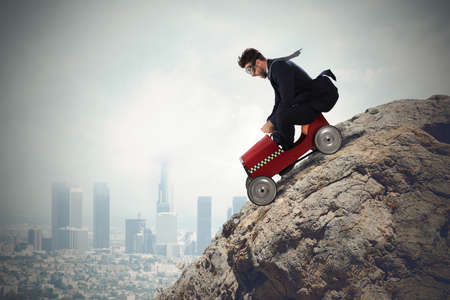 Businessman climb a mountain with a small car. Difficult carrer concept Stock Photo