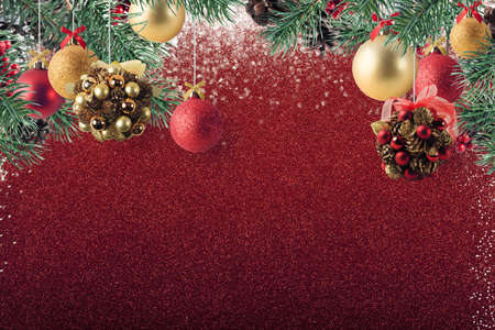 Xmas decoration with balls and pine cone on sparkly red glitter background