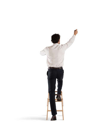Man on a ladder draws with a pen Stock Photo