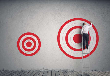 Businessman on a scale draws a big target. Achieve more important goals in work concept Reklamní fotografie