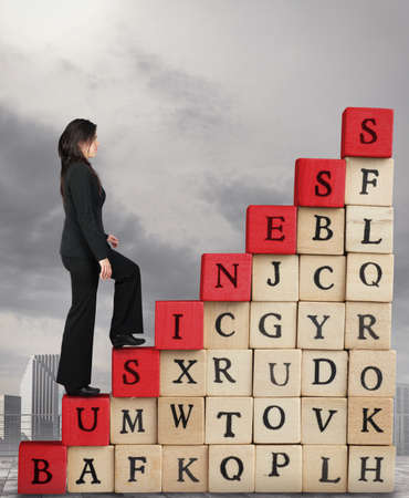 business letters: Businesswoman climbs a staircase cubes wooden letters with written business. Climb to increase success in business concept