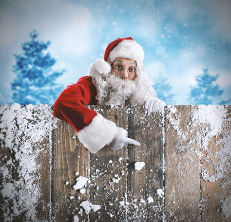 Marveled Santa Claus indicates a wooden board on snowy landscape