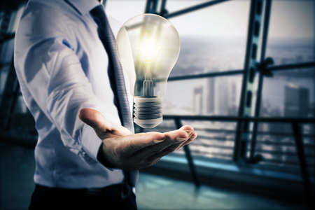 lamp light: Businessman holding a big light bulb. Great business idea concept Stock Photo