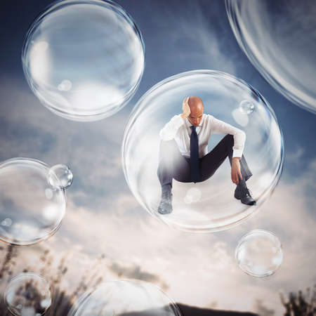 Sad businessman flies in a bubble. isolate themselves inside a bubble detachment from the outside world concept Фото со стока
