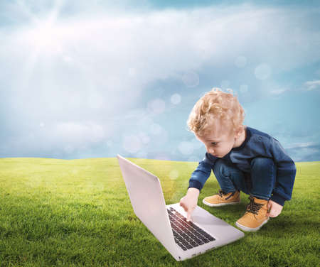 Child touching computer keys on a green lawn Stock Photo