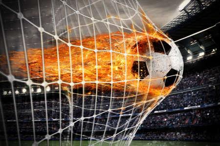 metas: puntajes de fútbol bola de fuego de una meta en la red Foto de archivo
