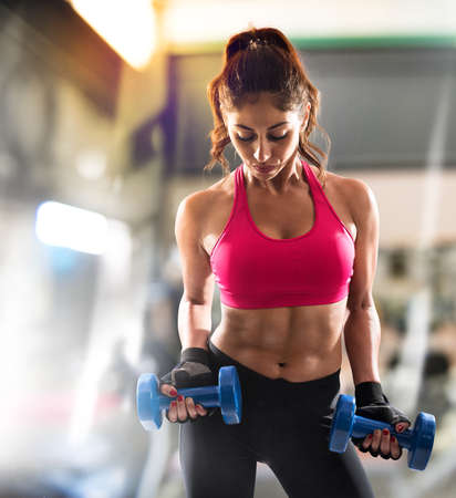 strong: Muscular woman is training at the gym