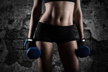 Athletic woman training biceps on grunge background