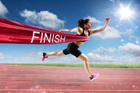 フィニッシュ ライン上の勝者の女性ランナー