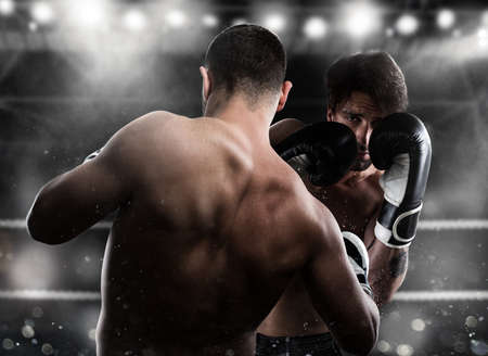 strong: Boxer in a boxe competition beats his opponent Stock Photo
