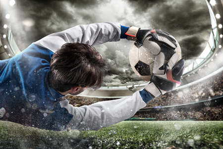 El portero coge el balón en el estadio Foto de archivo - 74640149