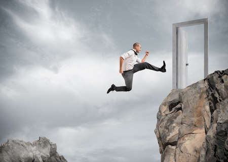 profession: Businessman jumping over the mountains to reach a door Stock Photo