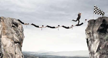 ビジネスマンは、フラグを得るためにブリッジをサポートします。達成ビジネス目標概念 写真素材