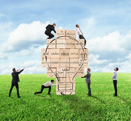 新しい創造的なアイデアを構築しています。事業者が一緒に描かれた電球で大きなレンガの壁を構築