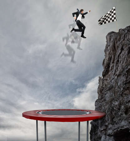 profession: Businessman jumping on a trampoline to reach the flag. Achievement business goal and Difficult career concept