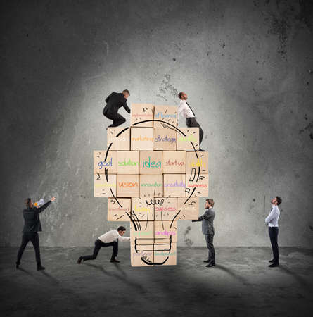 idea: Building a new creative idea. Business person built together a big brick wall with drawn lightbulb Stock Photo