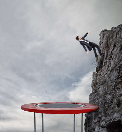 Businessman jumping on a trampoline to reach the flag. Achievement business goal and Difficult career concept