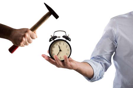 Hombre que sostiene un reloj despertador roto por un martillo Foto de archivo - 76548368
