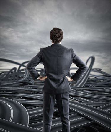 Confused businessman on a tangle of winding roads Stock Photo