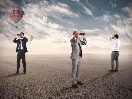 Zakenmensen op zoek naar nieuwe baan mogelijkheden met een verrekijker