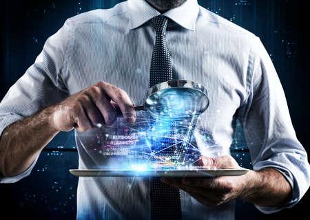 El hombre mira la lupa de la pantalla de una tableta