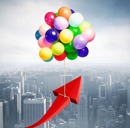 Pijl opgewekt door vliegende ballonnen. Vliegen naar economisch succes