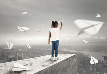 Little girl throws paper airplanes from a roof over the city