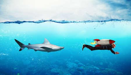 Concepto de la competencia con el hombre de negocios que se escapa de los tiburones con el cohete Foto de archivo