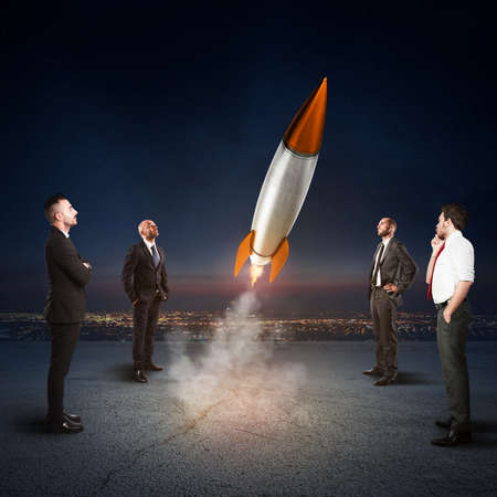 Team of businesspeople looks start a missile. Concept of company startup and new business. 3D Rendering. photo