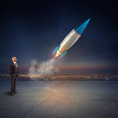 aspirational: Businessman looks start a missile. Concept of company startup and new business. 3D Rendering.