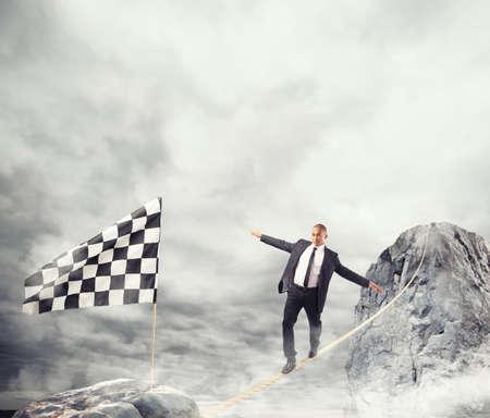 Concepto de negocio de hombre de negocios que superan los problemas de llegar a la bandera en una cuerda Foto de archivo