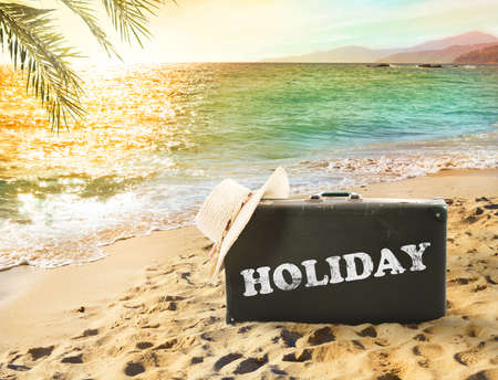 vintage background: Suitcase in a tropical beach with holiday writing during sunset