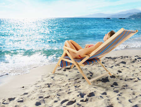 Girl tans on a deck chair on a beautiful beach Stock Photo
